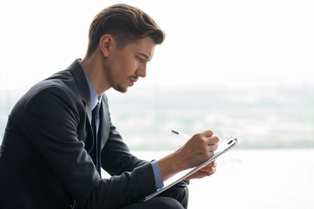 Focused adult businessman holding clipboard, writing on it and sitting in front of window with light view outside. Side view.