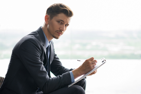 tensed: Pensive middle-aged businessman looking at camera, holding clipboard, writing on it and sitting in front of window with light view outside. Side view.