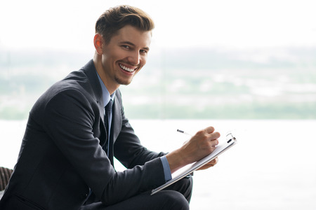 Smiling at camera middle-aged businessman holding clipboard, writing on it and sitting in front of window with light view outside. Side view.
