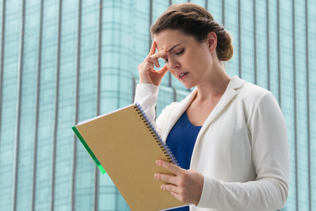tensed: Closeup of tense middle-aged businesswoman frowning, touching forehead, holding notebook and standing in front of big blurry building. Low angle view.
