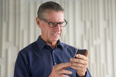 is disgusted: Closeup portrait of disgusted senior man holding smartphone and looking on its screen with wall in background