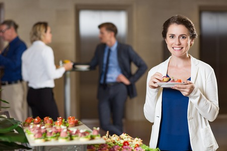 standing reception: Closeup of smiling at camera beautiful middle-aged woman eating snacks from plate and standing at table with food at buffet reception with blurry people in background