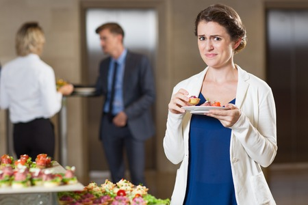 Closeup of looking at camera disgusted beautiful middle-aged woman tasting snacks from plate and standing at table with food at buffet reception with blurry people in background