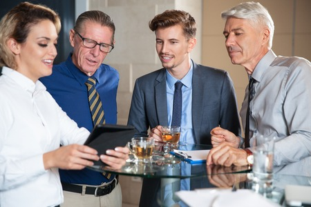 Smiling businesswoman showing something on tablet PC screen to three male colleagues. They are drinking tea and standing around table in cafe.
