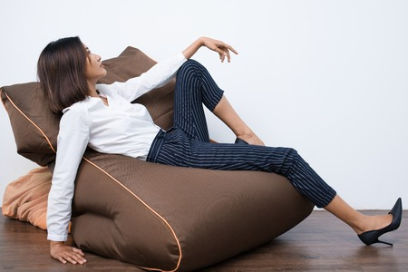 girl shoes: Pretty young Asian woman lying on beanbag chair in relaxed pose. Side view. Stock Photo
