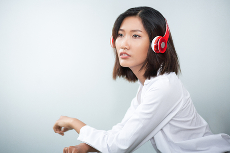 Closeup of content charming young Asian woman wearing headphones and listening to music