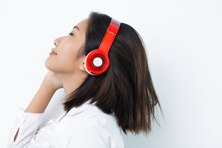 Closeup of content beautiful young Asian woman wearing headphones, closing eyes, listening to music. Side view.