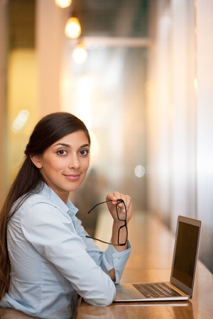 turn table: Portrait of smiling attractive middle-aged Indian woman looking at camera, holding glasses, sitting at table in cafe and working on laptop. Side view. Stock Photo