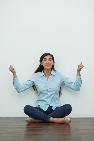 jubilating: Portrait of cheerful young woman sitting on floor in lotus position, looking at camera and pumping fists with white wall in background. Front view.
