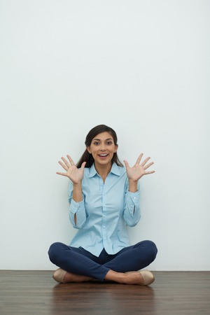 beine spreizen: Portrait of smiling at camera young woman sitting on floor with crossed legs and showing palms with spread fingers and white wall in background. Front view.