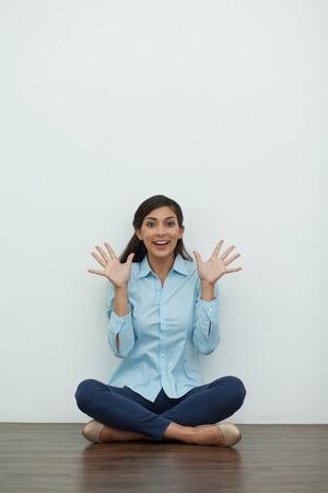 beine spreizen: Portrait von lächelnd in die Kamera junge Frau sitzt auf dem Boden mit gekreuzten Beinen und Palmen mit gespreizten Fingern und weiße Wand im Hintergrund. Vorderansicht.