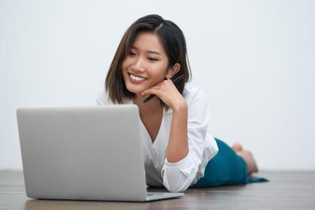 Close-upportret van glimlachende jonge mooie Aziatische vrouw die op vloer liggen en aan laptop computer met witte muur op achtergrond werken