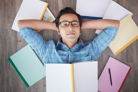 Serious Vietnamese college student in eyeglasses lying on parquet with hands behind head surrounded with copybooks and looking at camera Stock Photo