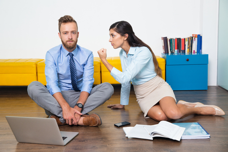 Sad young businessman looking at camera, when angry businesswoman showing fist to him. She threatening colleague. They working on common project. Business concept