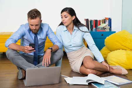 young entrepreneurs: Busy man using phone to text message, woman looking at him. They sitting on floor and working as team. Business items in mess on floor. Young entrepreneurs starting own business. Business concept