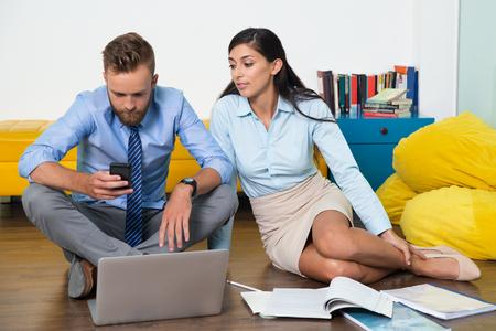 jovenes emprendedores: Hombre ocupado mediante teléfono al mensaje de texto, una mujer mirando a él. Se sienta en el suelo y trabajando como equipo. artículos de negocios en desorden en el piso. Los jóvenes empresarios que empiezan propio negocio. Concepto de negocio