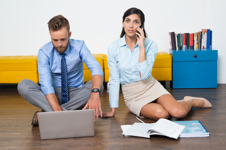catalogues: Concentrated businessman using laptop, young businesswoman talking on phone. They sitting on floor. Busy female manager consulting client on phone, catalogues placed near her. Home office concept