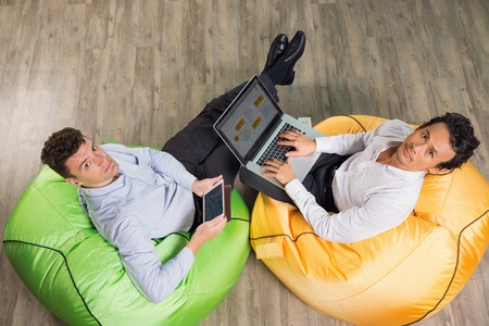 Two serious middle-aged men sitting on bright beanbag chairs in café, turning to camera and working on laptop computer and tablet. Top view. Stock Photo