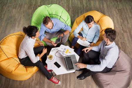 Vier actieve jongeren zitten op zitzakken rond de tafel in cafe, werken en bespreken van ideeën. Hoge hoekmening. Stockfoto