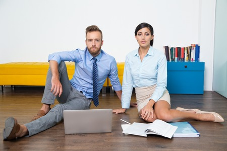 catalogues: Two serious young business people looking at camera and sitting on floor. Laptop, catalogues are on floor. Portrait of concentrated multiethnic managers at home office. Business concept Stock Photo