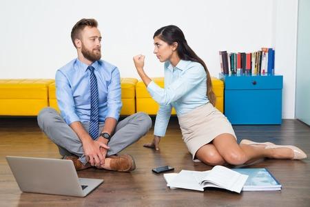 affari arrabbiata collega minaccioso. Donna furiosa mostra pugno all'uomo. Si siede sul pavimento e lavorare insieme. concetto di business