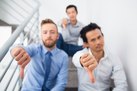 Group of multiethnic businessmen showing thumb down. Serious managers sitting on stairs and looking at camera. Focus on hand sign. They expressing disapproval. Failure concept Stock Photo