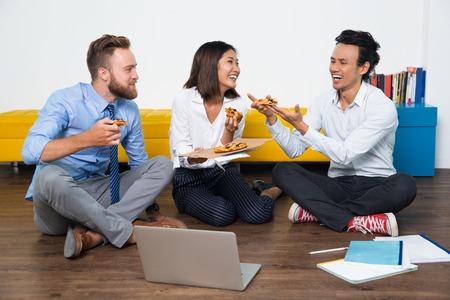 Felice squadra multietnica di tre giovani colleghi di lavoro che hanno pausa in ufficio, sono seduto sul pavimento, mangiare la pizza e ridendo