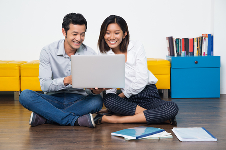 computer lessons: Cheerful Asian young business team using laptop and sitting on floor. Happy students surfing the net on portable computer to prepare for lessons. Business or education concept Stock Photo