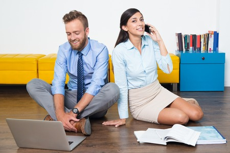they are watching: Happy businessman watching video or talking on skype, positive businesswoman using phone. Young entrepreneurs working together at home. They sitting on floor. Startup, business concept Stock Photo