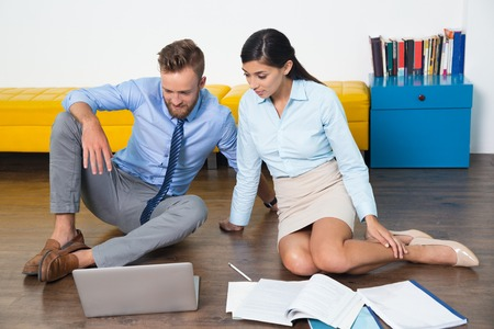 Young businessman and businesswoman using laptop. They looking at screen and sitting on floor. They watching video or talking on skype. Multiethnic people working in team. Business concept