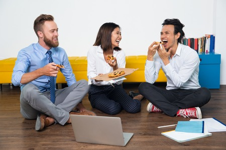 Laughing team of Asian and European business people having break in office or spending time at home of one of them after work. Colleagues communication, enjoying pizza and having fun Stock Photo