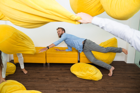 Cheerful Caucasian young man falling on couch to throw bean bag during crazy home party with friends. Beanbags flying all around