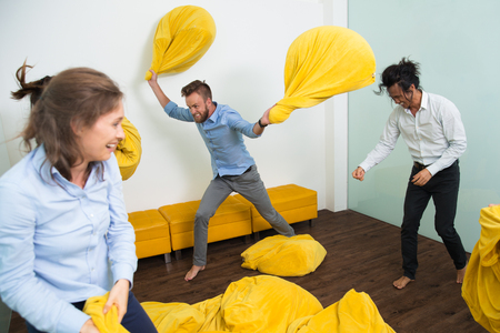 throw cushion: Crazy multiethnic young friends having cheerful meeting at home. Caucasian man fighting with two beanbags, woman and Asian man laughing and throwing beanbags