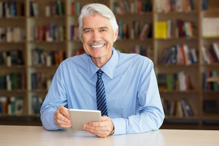 Portrait of cheerful senior Caucasian businessman wearing shirt and tie sitting in office or library with bookshelves behind him, holding touchpad and smiling at camera