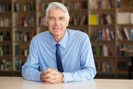 old desk: Portrait of confident senior Caucasian businessman or teacher wearing shirt and tie sitting at desk in office or classroom with bookshelves behind him Stock Photo