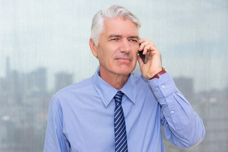 Portrait of frowning Caucasian senior executive having trouble talking on mobile phone to his partner