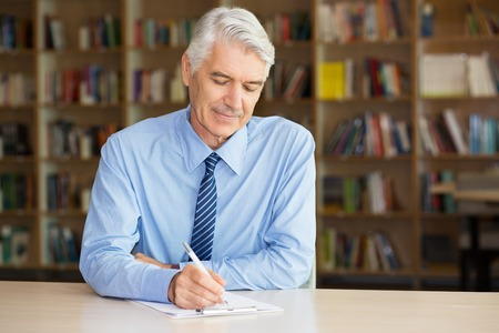 Calm senior businessman writing on paper and sitting at table in library. He concentrated on work and examining report. Gray-haired employee composing resume or cv