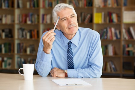 Thoughtful senior entrepreneur writing business plan. Pensive businessman touching forehead with pen. He looking aside and sitting at table in cafe or library