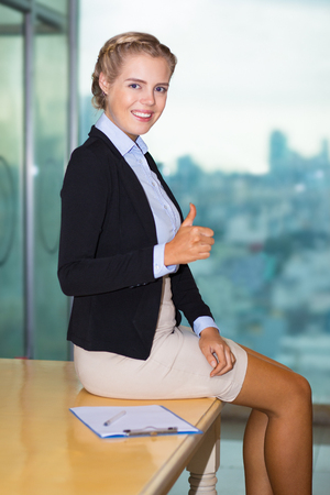 Portrait of positive confident beautiful young business woman looking at camera, showing thumb up and sitting on caf? table with big window in background