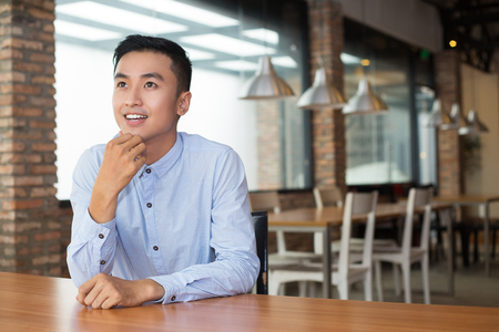 nowhere: Closeup portrait of smiling young Asian man looking at nowhere, dreaming, touching chin and sitting at empty table with blurred cafe interior in background