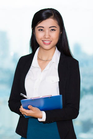 fascinating: Closeup portrait of smiling  fascinating young businesswoman looking at camera, standing, holding clipboard, writing and conducting survey