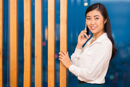 wooden partition: Closeup portrait of smiling charming young Asian woman looking at camera, calling on phone and touching wooden partition with blurred view in background