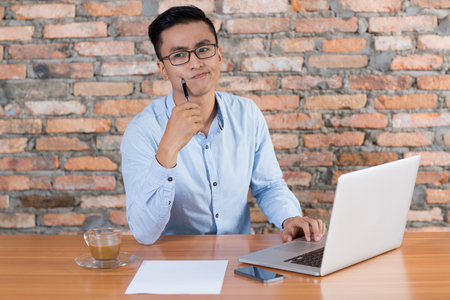 Puzzled young business man thinking, working on laptop computer and sitting at office desk with brick wall in background