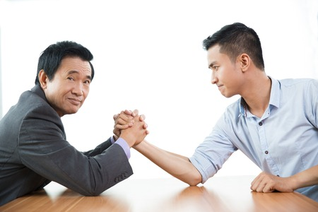 rival: Senior and young business men arm wrestling at table. Confident senior man is looking at camera and holding rival hand with both hands. Isolated view on white background.