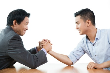 aggressively: Senior and young business men arm wrestling aggressively at table and looking at each other. Isolated view on white background.
