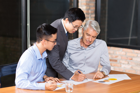 Geconcentreerde multi-etnische zakenlieden die met documenten op vergadering werken. Hogere Aziatische leider die op papier schrijft wanneer het verklaren van businessplan. Teamwork concept