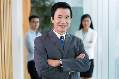mature business man: Portrait of senior Asian businessman wearing formal suit looking at camera and smiling with arms crossed, his team standing in background Stock Photo