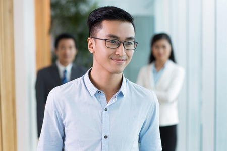 Portrait of positive young Asian businessman wearing shirt and eyeglasses looking away, his team standing in background