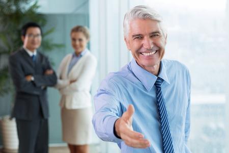 Portret van lachende senior blanke zakenman draagt overhemd en stropdas uitbreiding van de hand voor handdruk te begroeten of feliciteren met zijn partner of werknemer en breed lachend, team staan in de achtergrond Stockfoto