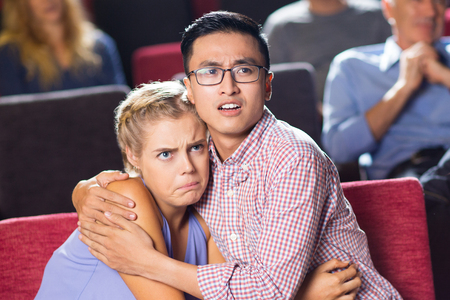 Portrait of shocked multiethnic young couple, Asian man and Caucasian woman, sitting in cinema, watching horror and hugging